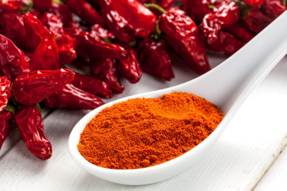 A spoon of paprika with red peppers